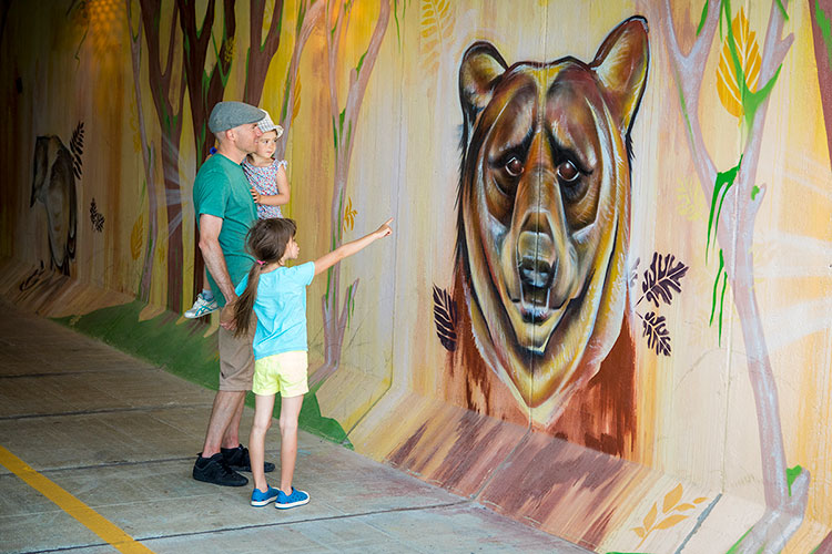 A father with two children stop to look at a bear mural in a Whistler underpass.