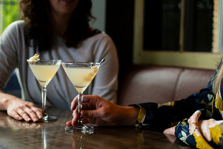Two women sit drinking Parmesan Martinis at The Raven Room in Whistler.