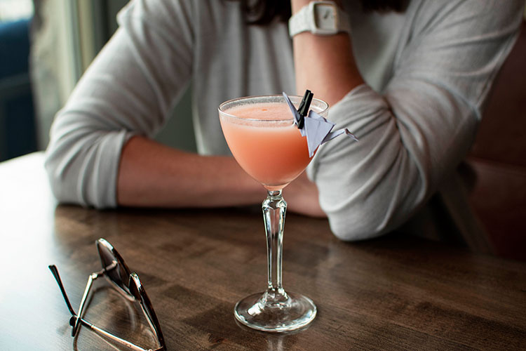 A woman drinks a vibrant pink cocktail called the Paper Crane at The Raven Room in Whistler.