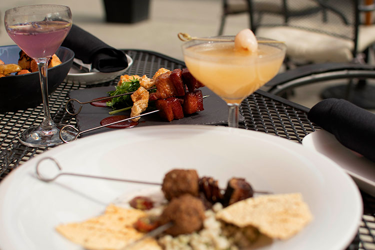 Lamb and pork skewer dishes served on the Bearfoot patio with colourful cocktails.
