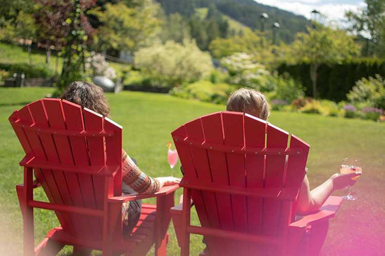 Two women sit in large deck chairs in the gardens of the Fairmont in Whistler, with cocktails in hand.