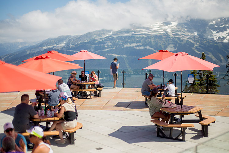 Picnic tables with red umbrellas on a large patio with mountain views on Whistler Blackcomb.