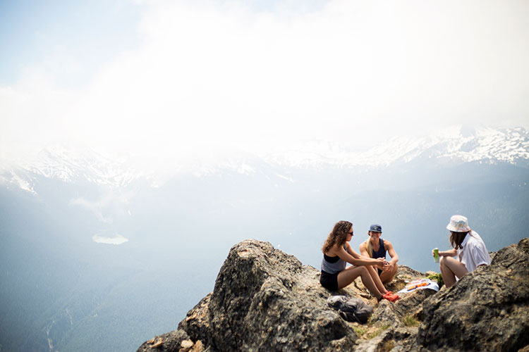 Three hikers sit on the rocks with incredible views of the Coast Mountain all around them on Whistler Blackcomb.