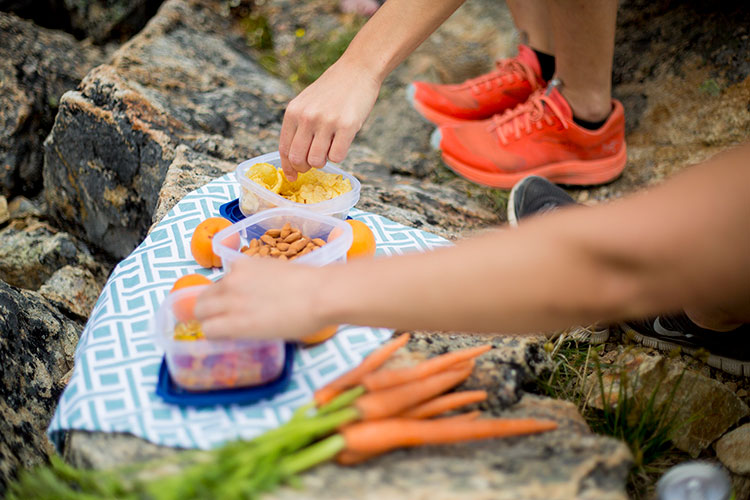 A selection of picnic nibble laid out on rocks.