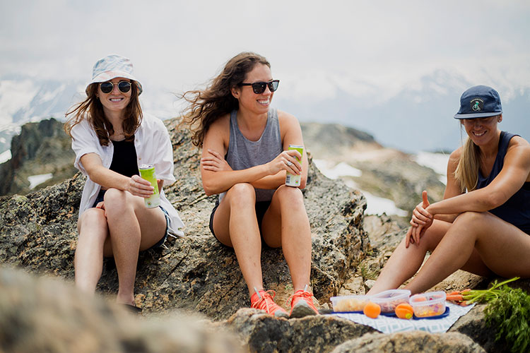 Three hikers sit on rocks in the alpine and enjoy a picnic with a view on Whistler Blackcomb.
