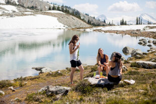 Three hikers have a picnic on the shores of an alpine lake on Whistler Blackcomb.