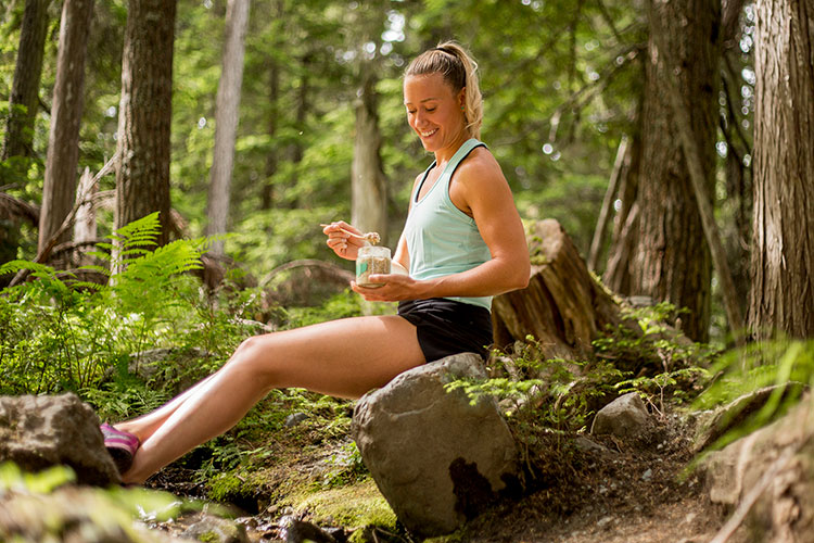 A hiker sits on a log and has a snack while heading up the Ascent Trail on Blackcomb Mountain in Whistler.
