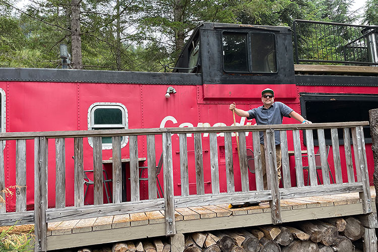 Allan Crawford, owner of Canadian Wilderness Adventures poses by the caboose at their base in the Callaghan Valley.