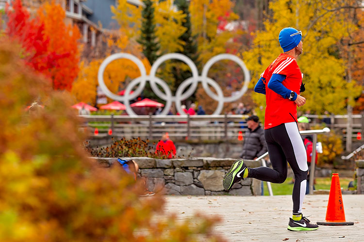 A runner comes into Whistler Village at the end of the Whistler 50 Relay and Ultra amidst the fall colours.