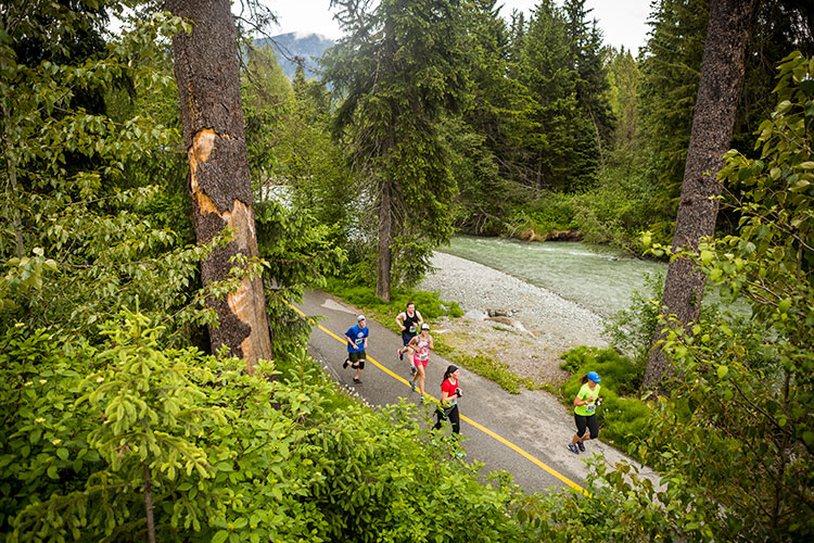 Runners head down the Whistler Valley Trail between a river and the forest in the Whistler Half Marathon.