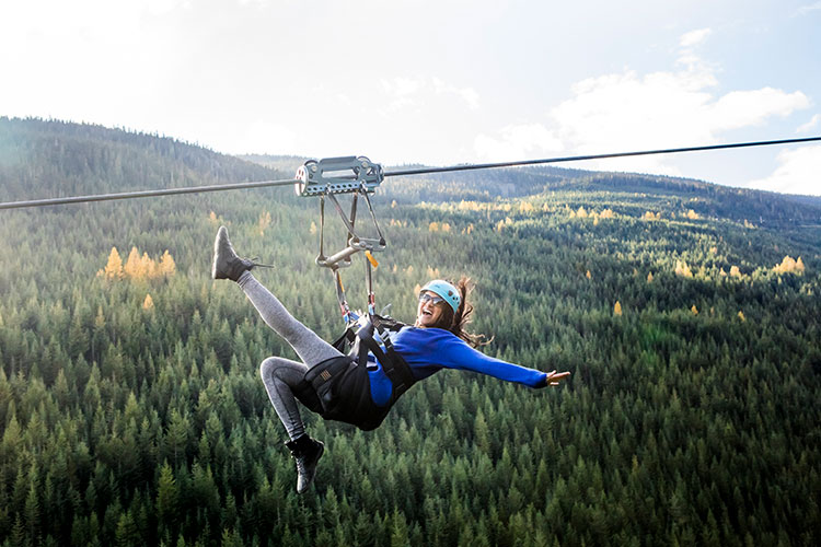 A woman zips across the Whistler Valley on a zipline, the fall forest underneath her.