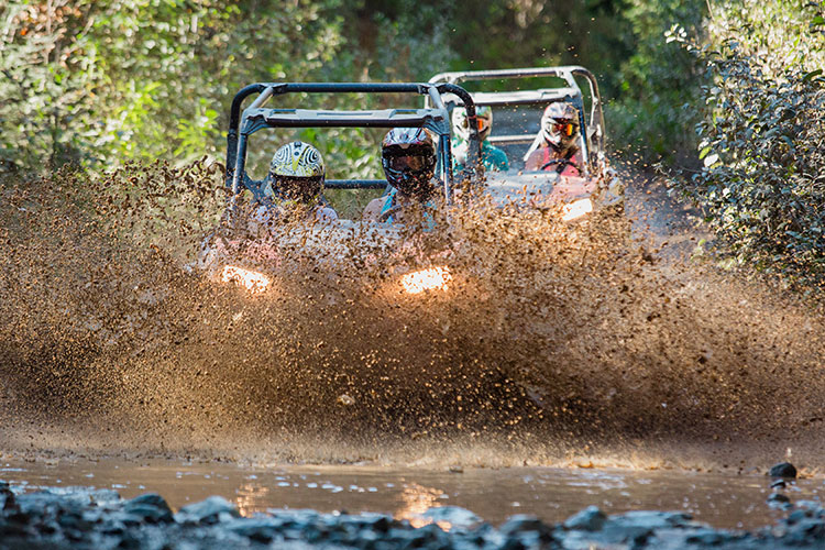 Two RZRs power through a muddy puddle in Whistler.