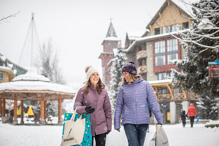 Two women carry shopping bags down the Village Stroll in Whistler.