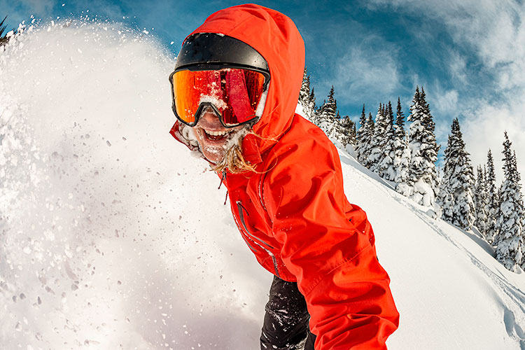 A snowboarder looks directly at the camera as they complete a powdery turn on Whistler Blackcomb.