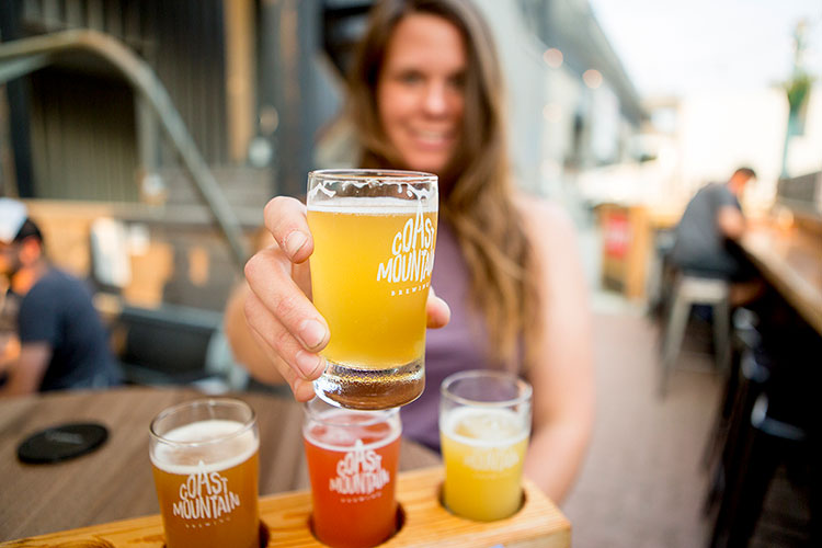 A woman holds up one of her samples from a flight of beers at Coast Mountain Brewing in Whistler.