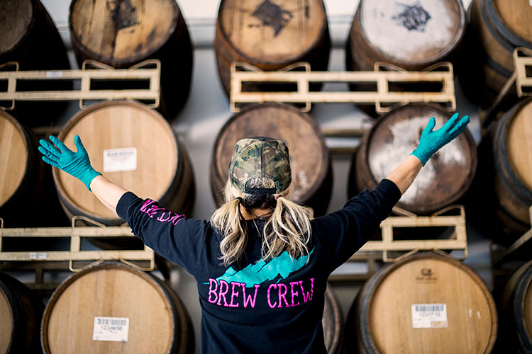 A brewer stands in front of barrels in the brewery area of Coast Mountain Brewing in Whistler.