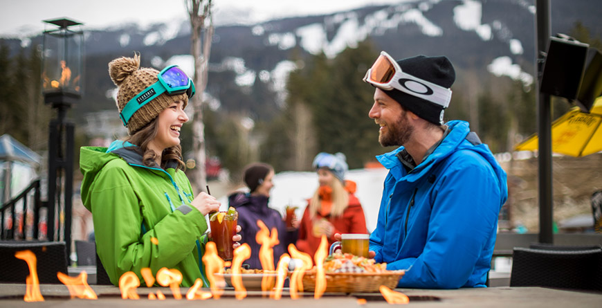 Two people enjoying apres on a patio in winter in Whistler BC