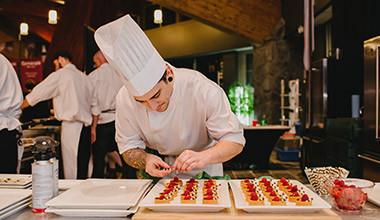 A chef putting the final touches on food at Crush at Cornucopia in Whistler, BC