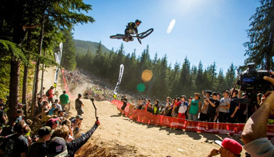 Mountain biker mid-air performing tricks for a crowd on onlookers.