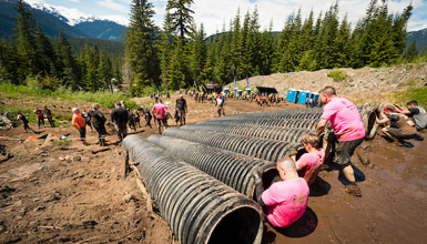 A muddy team of Tough Mudder participants run through the final obstacle.