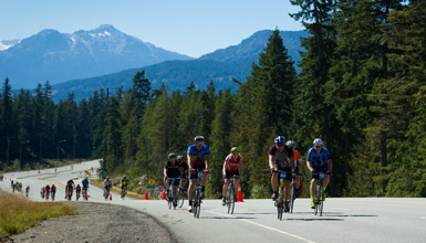 GranFondo Whistler particpants coming over the crest of a hill along the Sea to Sky corridor.