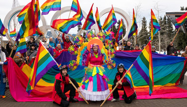 People in costume fly out the WinterPride giant rainbow flag