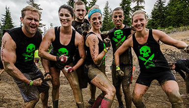 A muddy team of Tough Mudder participants at Whistler Olympic Park in Whistler BC.