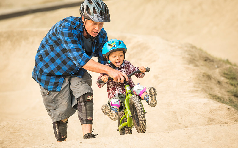 Giving a boost to his child on the pump track