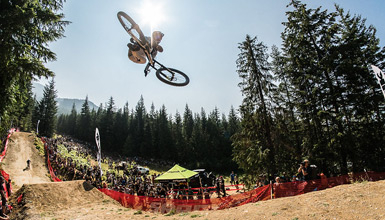Mountain biker performing mid-air tricks for a crowd at Crankworx in Whistler BC