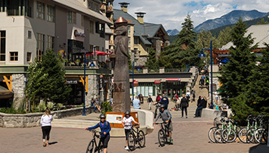 Bikers walking along the Village Stroll in Whistler