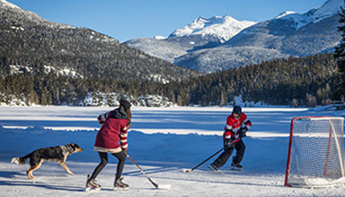 People playing hockey with a dog on frozen Alta Lake in Whistler