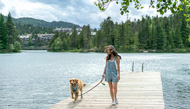 Woman walking with dog on dock at Alpha Lake Park