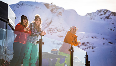 Skiers enjoying a sunny mountaintop patio on a spring day in Whistler