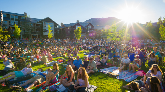 People sitting on the lawn for a concert
