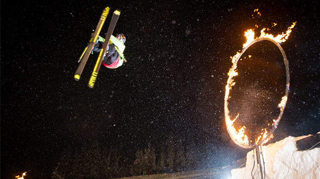 A skiier jumps through a ring of fire