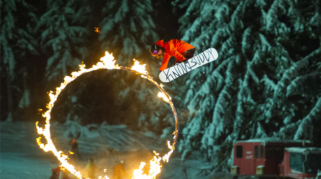 A snowboarder jumps through a ring of fire
